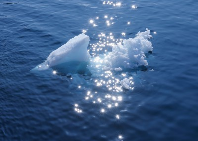 Ice chunk with sparkling sunlight on ocean, Icefjord, Ilulissat, Greenland,